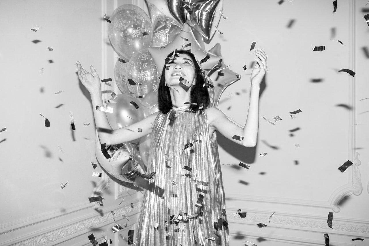 Blije vrouw in feestjurk met ballonnen en slingers